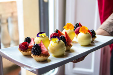 Mono-Portions of tartlet with red fruits and white chocolate sphere.